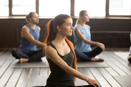 Photo portrait of attractive yogi woman and a group of young sporty people in parivrtta sukhasana pose, students working out in club, indoor, studio