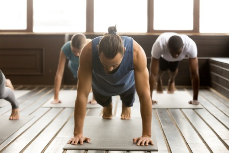Group of young sporty people practicing yoga lesson standing in Plank pose, doing Push ups or press ups exercise, working out, indoor full length, studio