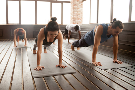 Group of young sporty people practicing yoga lesson standing in Plank pose, doing Push ups or press ups exercise, working out, indoor full length, studio floor Stock Photo
