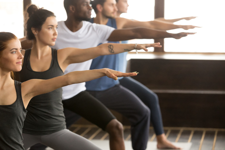 Group of young sporty afro american and caucasian people practicing yoga lesson, standing in Warrior two exercise, Virabhadrasana II pose, working out, indoor close up, studio