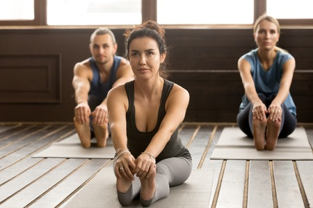 Young smiling sporty woman and a group of people practicing yoga lesson, stretching in paschimottanasana exercise, Seated forward bend pose, working out, indoor, studio. Healthy lifestyle concept
