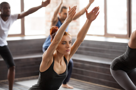Group of young afro american and caucasian sporty people practicing yoga lesson standing in Chair exercise, Utkatasana pose, working out, indoor close up, studio. Healthy lifestyle concept 스톡 콘텐츠