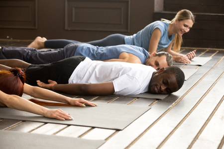 Tired diverse african and caucasian people relaxing smiling having fun lying on mat floor at yoga class, resting to relieve tight muscles after workout group training, stretching relaxation concept Imagens