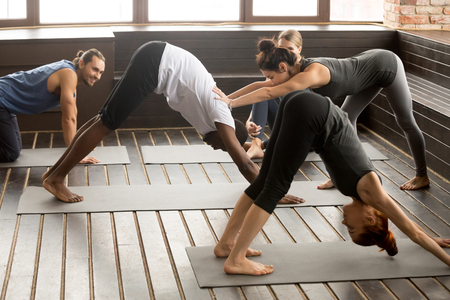 Yoga fitness instructor teacher helping african man beginner doing stretching downward facing dog exercise standing in adho mukha svanasana pose at studio group training class with multiracial people.