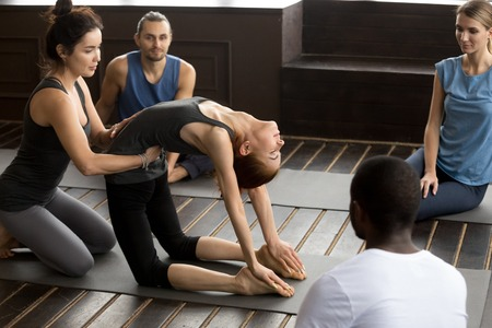 Yoga teacher assisting young woman in doing ustrasana exercise, learning new camel pose, diverse people working out practicing pilates together in studio at group training class with instructors help Stock Photo
