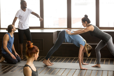 Yoga teacher assisting woman doing downward facing dog exercise standing in adho mukha svanasana pose, fitness instructor helping in stretching on mat at group training class with diverse people