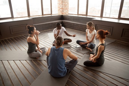 African american yoga instructor talking to diverse group sitting on mat in studio, multiracial happy people having conversation about healthy mindful life and motivation at training seminar class 版權商用圖片