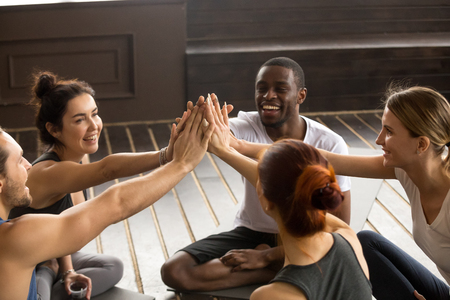 Fit sporty happy multicultural people giving high five at yoga training, motivated multiracial group unite joining hands together as concept of team support in fitness achievements and mindful life Reklamní fotografie