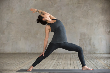 Young woman practicing yoga, doing Reverse Warrior exercise, Viparita Virabhadrasana pose, working out, wearing sportswear, black pants and top, indoor full length, gray wall in yoga studio