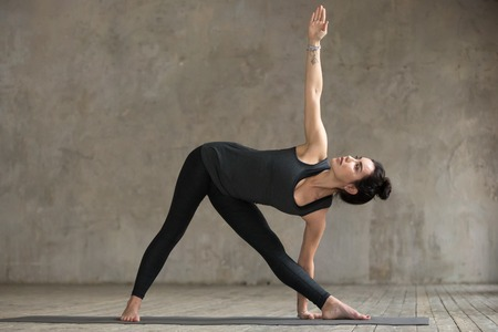 Young woman practicing yoga, doing Utthita Trikonasana exercise, extended pose, working out, wearing sportswear, black pants and top, indoor full length, gray wall in yoga studio