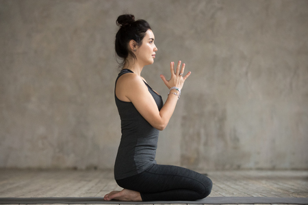 Young woman practicing yoga, doing seiza exercise, vajrasana pose, working out, wearing sportswear, black pants and top, indoor full length, gray wall in yoga studio