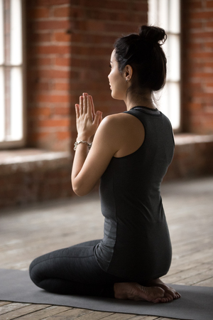 Young woman practicing yoga, doing seiza exercise, vajrasana pose, working out, wearing sportswear, black pants and top, indoor full length, yoga studio, rear view Stock Photo