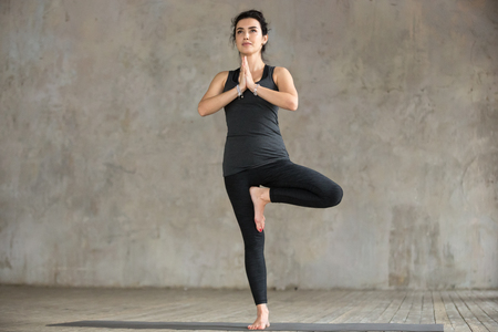 Young sporty woman practicing yoga, doing Vrksasana exercise, Tree pose, working out, wearing sportswear, black pants and top, indoor full length, gray wall in yoga studio