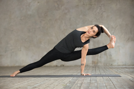 Young sporty woman practicing yoga, doing Visvamitrasana exercise, arm balance pose, working out, wearing sportswear, black pants and top, indoor full length, gray wall in yoga studio 免版税图像