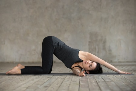 Young sporty woman practicing yoga, doing thread the needle exercise, spine bend pose, working out, wearing sportswear, black pants and top, indoor full length, gray wall in yoga studio, side view