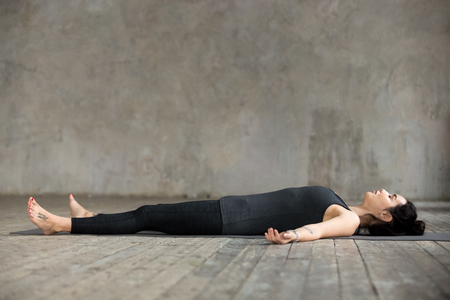 Young sporty woman practicing yoga, lying in Dead Body or Corpse pose, Savasana exercise, working out, resting after practice, indoor full length, gray wall in yoga studio