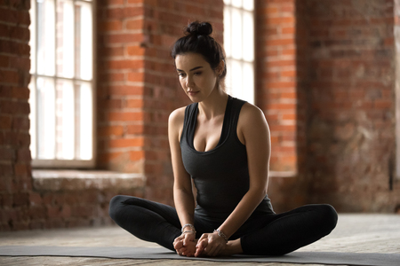 Young sporty woman practicing yoga, doing Butterfly exercise, baddha konasana pose, working out, wearing sportswear, black pants and top, indoor full length, yoga studio