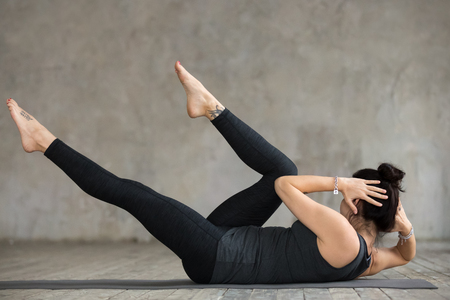 Young slim woman practicing fitness, doing crisscross exercise, bicycle crunches pose, working out, wearing sportswear, black pants and top, indoor full length, against gray wall in sport studio