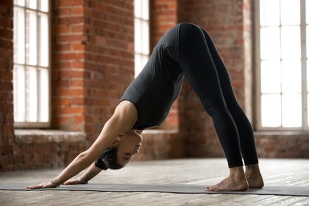 Young sporty woman practicing yoga, doing Downward facing dog exercise, adho mukha svanasana pose, working out, wearing sportswear, black pants and top, indoor full length, yoga studio