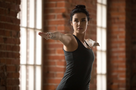 Young sporty woman practicing yoga, doing Warrior Two exercise, Virabhadrasana 2 pose, working out, wearing sportswear, black top, indoor close up, yoga studio