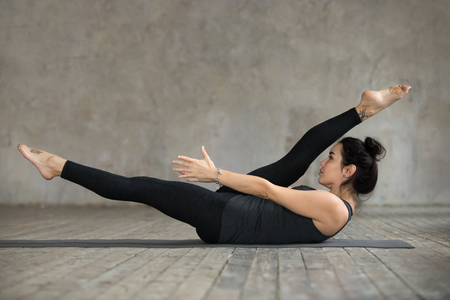 Young sporty woman practicing fitness, doing alternate leg stretch exercise, warm up pose, working out, wearing sportswear, black pants and top, indoor full length, against gray wall in sport studio Stock Photo
