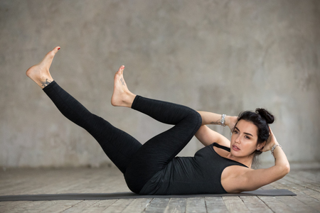 Young sporty woman practicing fitness, doing crisscross exercise, bicycle crunches pose, working out, wearing sportswear, black pants and top, indoor full length, against gray wall in sport studio