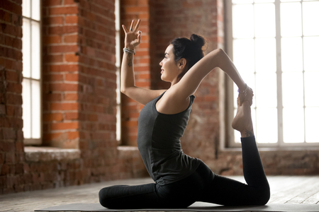 Young sporty woman practicing yoga, doing One Legged King Pigeon exercise, Eka pose, working out, wearing sportswear, black pants and top, indoor full length, yoga studio