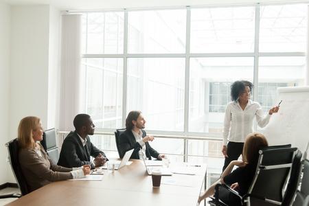 Afro-Amerikaanse zakenvrouw geeft presentatie aan diverse collega's tijdens vergadering, zwarte manager presenteert nieuw plan voor projectteam in directiekamer, kantoormedewerker verklaart bedrijfsidee op flipchart Stockfoto