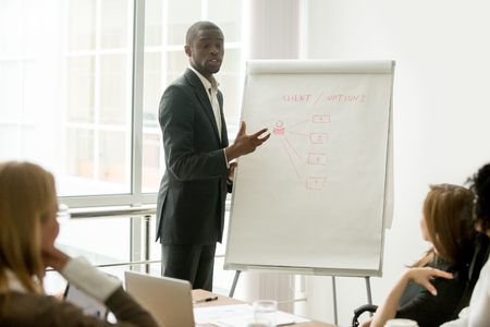 Confident african speaker gives presentation to multiracial sales team with flipchart, black businessman in suit presenting new marketing project speaking at seminar, business coach training managers Archivio Fotografico - 97042861