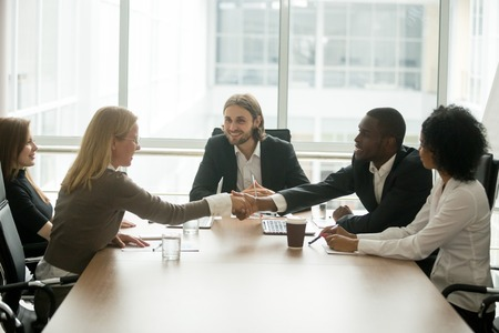 African businessman and caucasian businesswoman shaking hands over conference table at multiracial group meeting, diverse business team members handshaking starting collaboration, welcome new partner