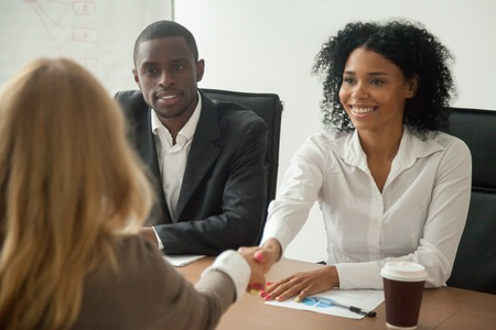 African american hr team welcoming female applicant at job interview, diverse businesswomen shaking hands at multi ethnic group meeting, handshaking and good first impression, teamwork introduction