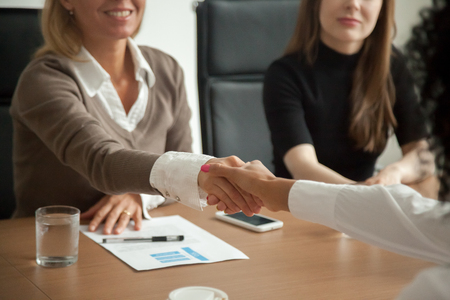 Caucasian hr manager welcoming african applicant at job interview, diverse businesswomen handshaking at group meeting, good first impression and female teamwork, women business partnership concept
