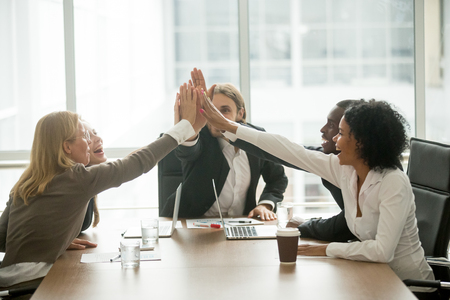 Happy motivated multiracial team giving high five at meeting, diverse group of colleagues join hands together celebrating corporate growth, successful teamwork, unity help support in business concept