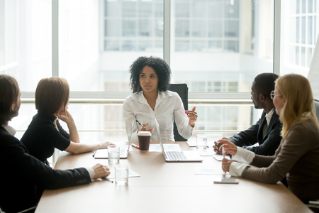Jefa negra que lidera la reunión del equipo multirracial corporativo hablando con diversos empresarios, mujer ejecutiva afroamericana discutiendo el plan del proyecto en una reunión grupal multiétnica en la sala de juntas