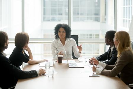 Schwarzer weiblicher Chef, der die gemischtrassige Unternehmensteambesprechung spricht mit verschiedenen Wirtschaftlern, Afroamerikanerfrauenexekutive bespricht Projektplan an der multiethnischen Anweisung der Gruppe im Sitzungssaal führt
