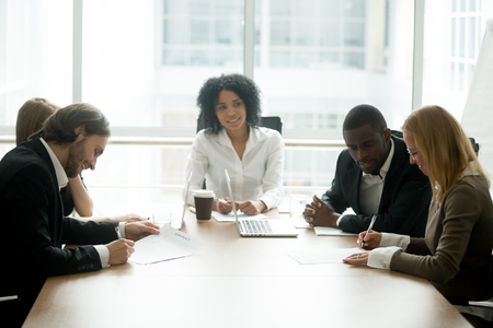Businessman and businesswoman signing contracts at group multiracial meeting, two smiling male and female new partners making deal after successful negotiations putting signature on business papers Banque d'images