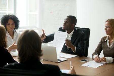 Empresario afroamericano en desacuerdo con los términos del contrato en las negociaciones multiétnicas grupales, socio negro discutiendo sobre las condiciones del acuerdo o estafa de fraude señalando el documento en la reunión multirracial