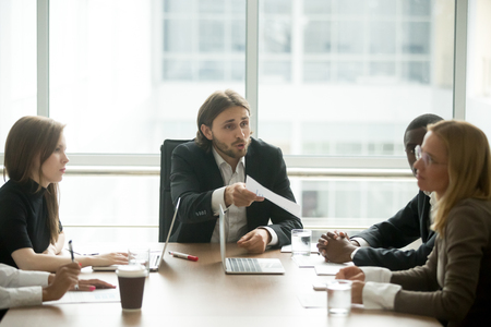 Angry boss reprimanding female employee for bad work result sitting at conference table, male ceo scolding incompetent manager blaming for mistake in financial report or failure at team group meeting