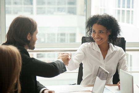 Donna di affari africana sorridente e uomo d'affari caucasico che stringono le mani alla riunione, handshake capo nero femminile che dà il benvenuto al nuovo partner felice di iniziare la collaborazione o fare una buona prima impressione