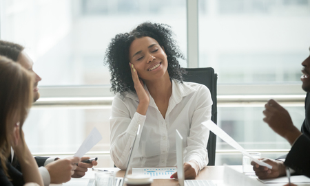 Absent-minded distracted black businesswoman dreaming of success and happiness at corporate group meeting, dreamy smiling african female boss thinking of new idea avoiding work stress lost in thought 版權商用圖片