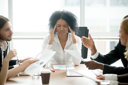 ストレスを感じたアフリカのビジネスウーマンは、企業の会議で疲れを感じ、チームブリーフィングで寺院に触れる頭痛に苦しむ疲れ果てた黒人女