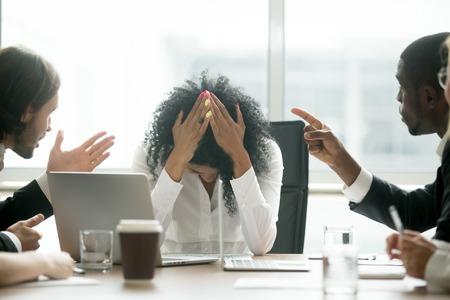 Boos depressieve zwarte vrouw leider die lijden aan discriminatie op grond van geslacht ongelijkheid op het werk, diverse mannen collega's wijzende vingers schelden pesten gefrustreerd Afrikaanse zakenvrouw op de werkplek