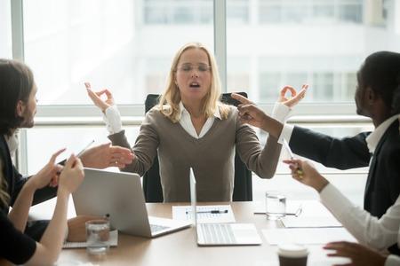 스트레스가 많은 직장에서 요가를 연습하는 스트레스를받은 사업가, 정신 건강과 정서적 균형을 유지하기위한 다양한 직원과의 회의에서 명상하는 임원 여성 보스, 스트레스 해소 없음 스톡 콘텐츠 - 97035002