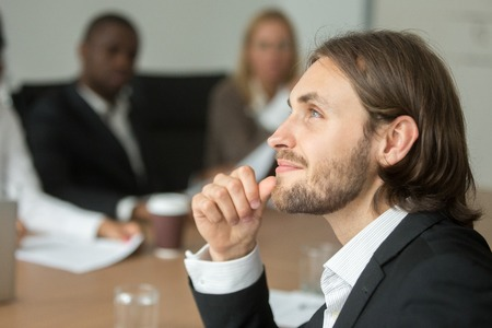 Dreamy businessman in suit looking to the future thinking of business success, smiling team leader making plans of project idea at work, aspirational manager dreaming of new opportunities, head shot Stock Photo