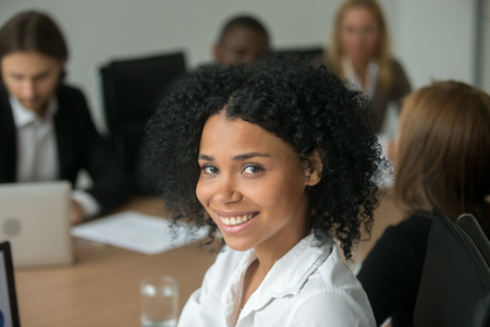 African american attractive businesswoman at meeting, smiling black employee, team leader or professional manager looking at camera, young woman business coach or corporate teacher head shot portrait Stock Photo