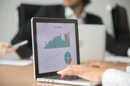 Die Geschäftsfrau, die mit statistischem Bericht bei der Teamsitzung analysiert Marketing-Ergebnis arbeitet, stellt Diagramme online auf Laptopschirm, Geschäftssoftware für Projektdatenanalysekonzept, Abschluss herauf Ansicht grafisch dar Standard-Bild