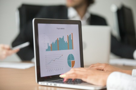 Businesswoman working with statistical report at team meeting analyzing marketing result graphs charts online on laptop screen, business software for project data analysis concept, close up view Archivio Fotografico