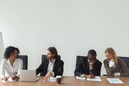 Diverse business people working talking sitting at conference table, african and caucasian employees discuss plans in boardroom, multiracial partners waiting for meeting to start, corporate teamwork Stock Photo