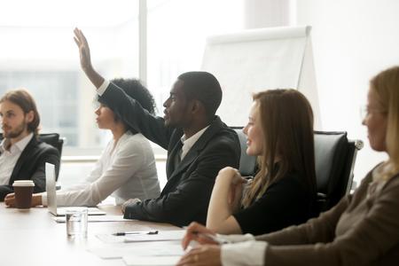 Empresario afroamericano levantando la mano en la reunión del equipo diverso, el oyente participante de capacitación negro hace preguntas durante el seminario de negocios sentado en la mesa de conferencias, educación grupal corporativa