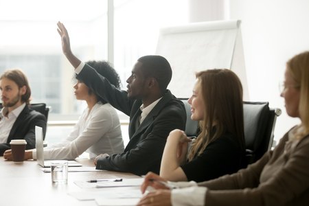 African american businessman raising hand at diverse team meeting, black training participant listener man asks question during business seminar sitting at conference table, corporate group education